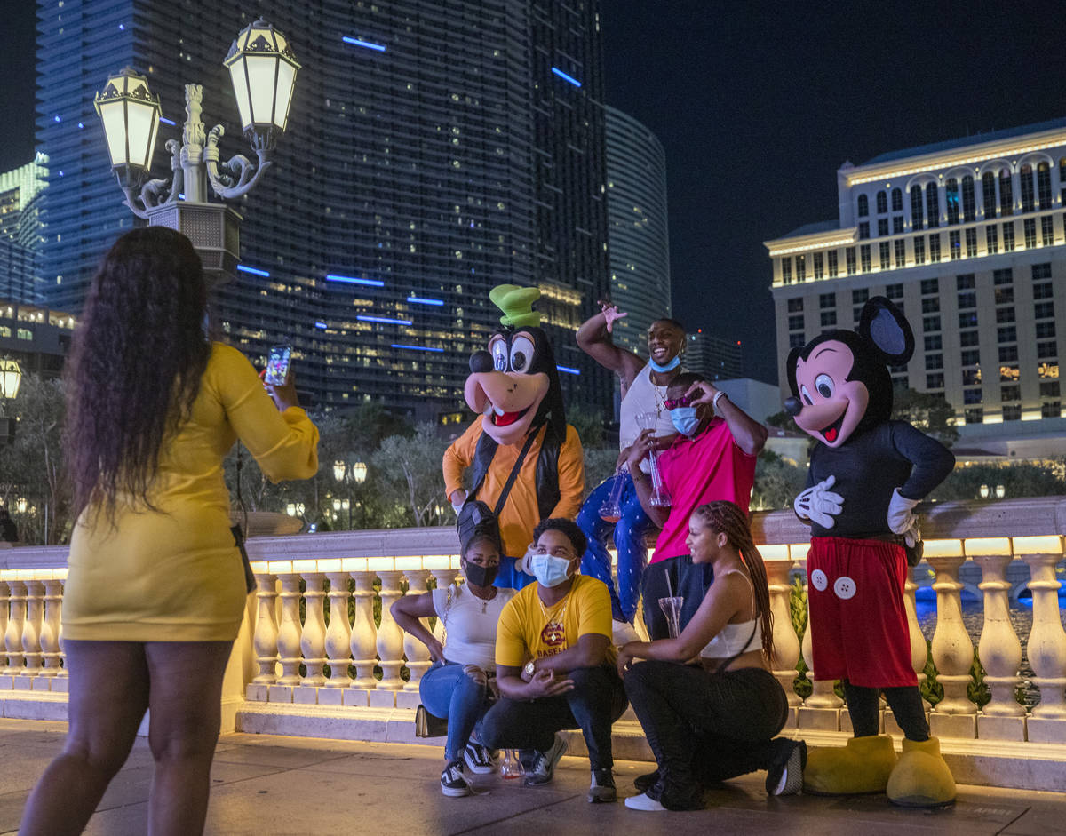 Tourists get their photo taken near the Bellagio hotel and casino fountains, late Friday night ...