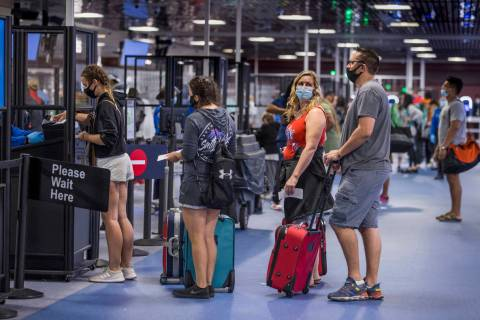 Passengers make their way through the TSA checkpoint in Terminal 1 as COVID-19 safety precautio ...