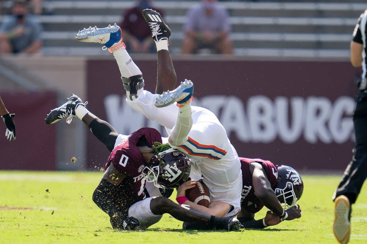Florida quarterback Kyle Trask (11) is tackled after a short gain by Texas A&M defensive linema ...