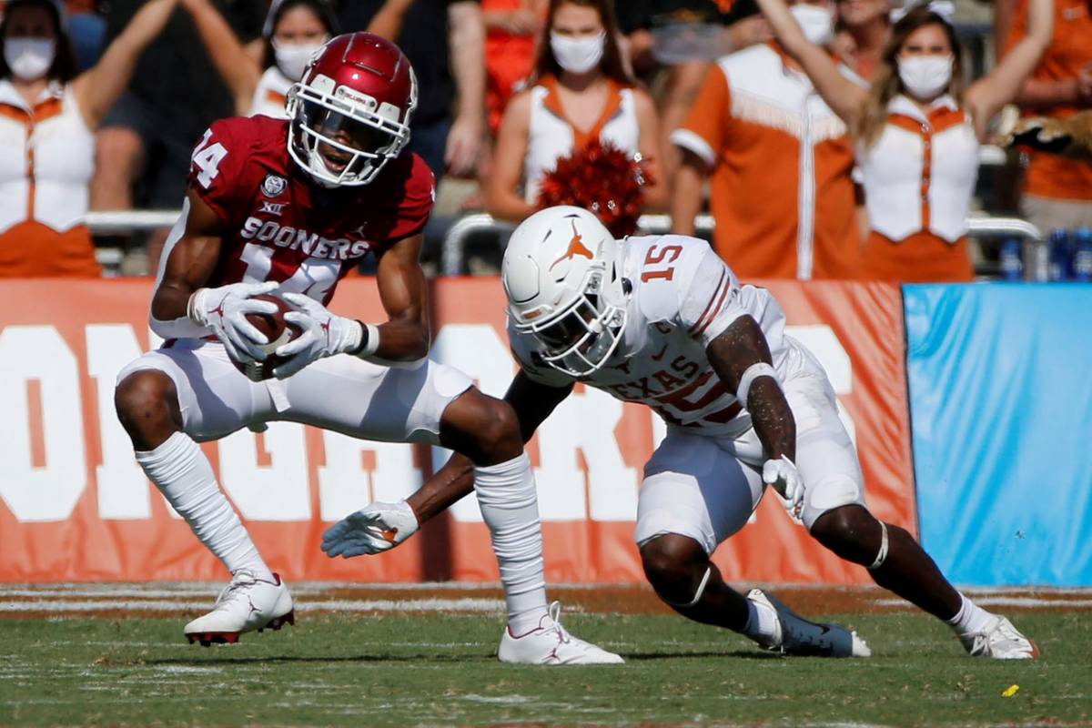 Oklahoma wide receiver Charleston Rambo (14) catches a pass in front of Texas defensive back Ch ...
