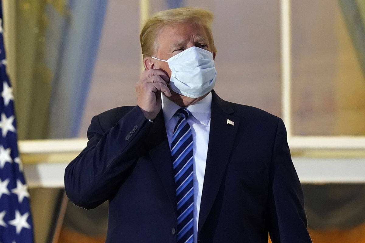 President Donald Trump removes his mask as he stands on the balcony outside of the Blue Room as ...