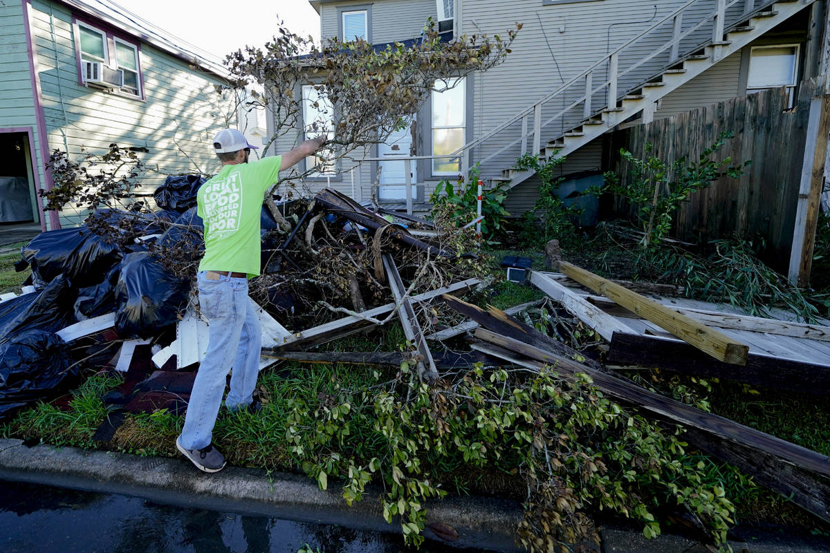 Caleb Cormier moves debris after Hurricane Delta moved through, Saturday, Oct. 10, 2020, in Lak ...