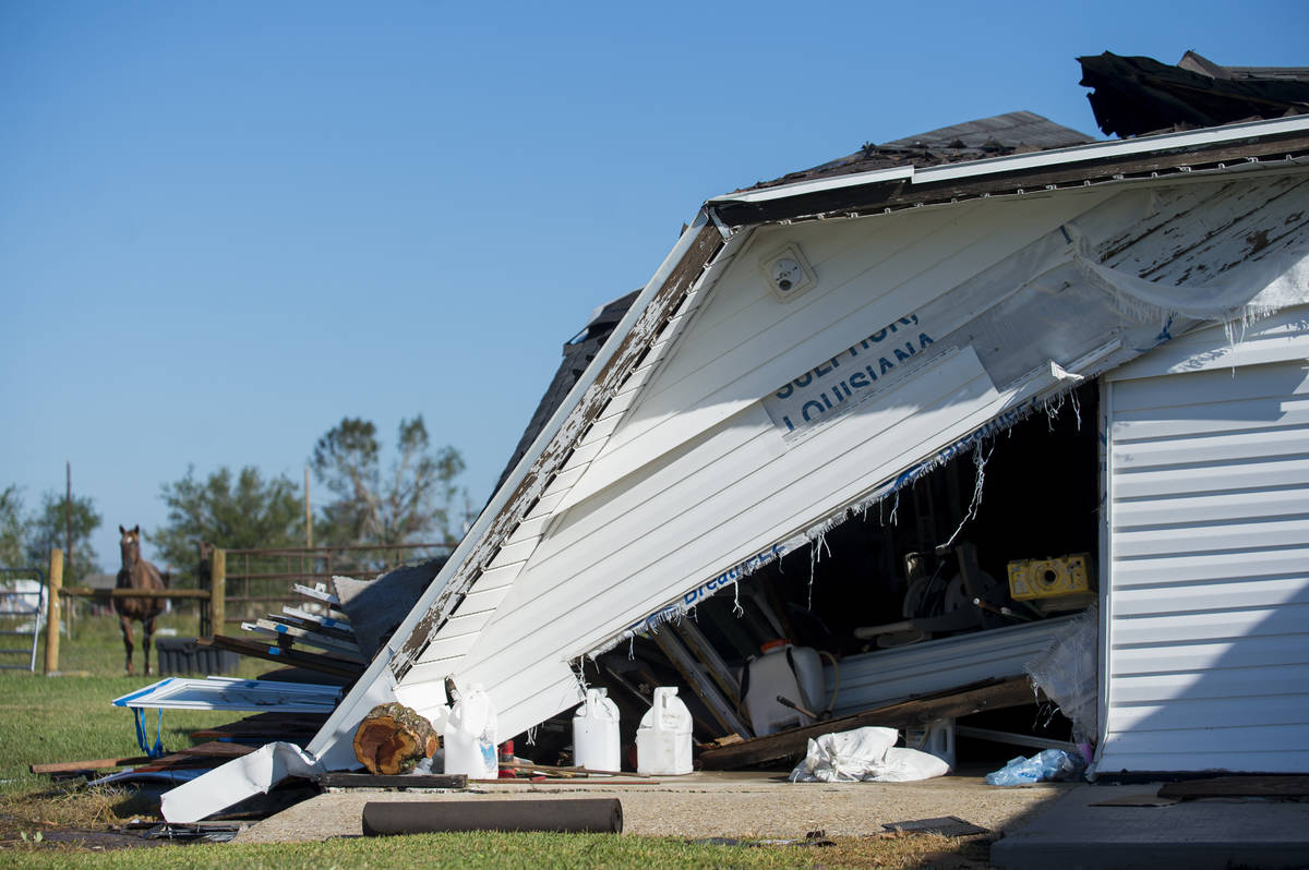 """A garage partially destroyed by Hurricane Laura has the word, """"Louisiana"""" written on ..."""