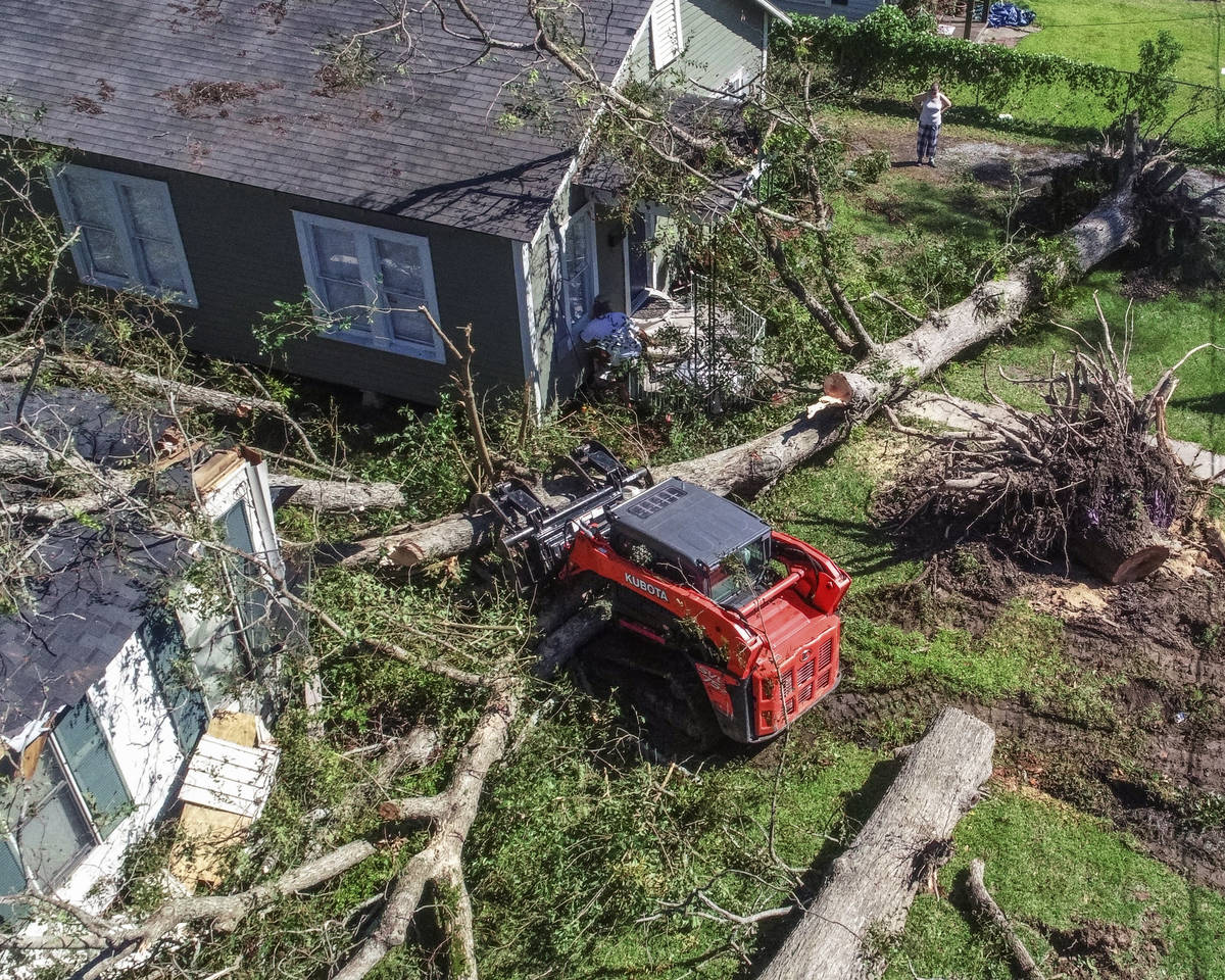 Trees are cleared that have fallen on houses during Hurricane Delta in Jennings, La., Saturday, ...