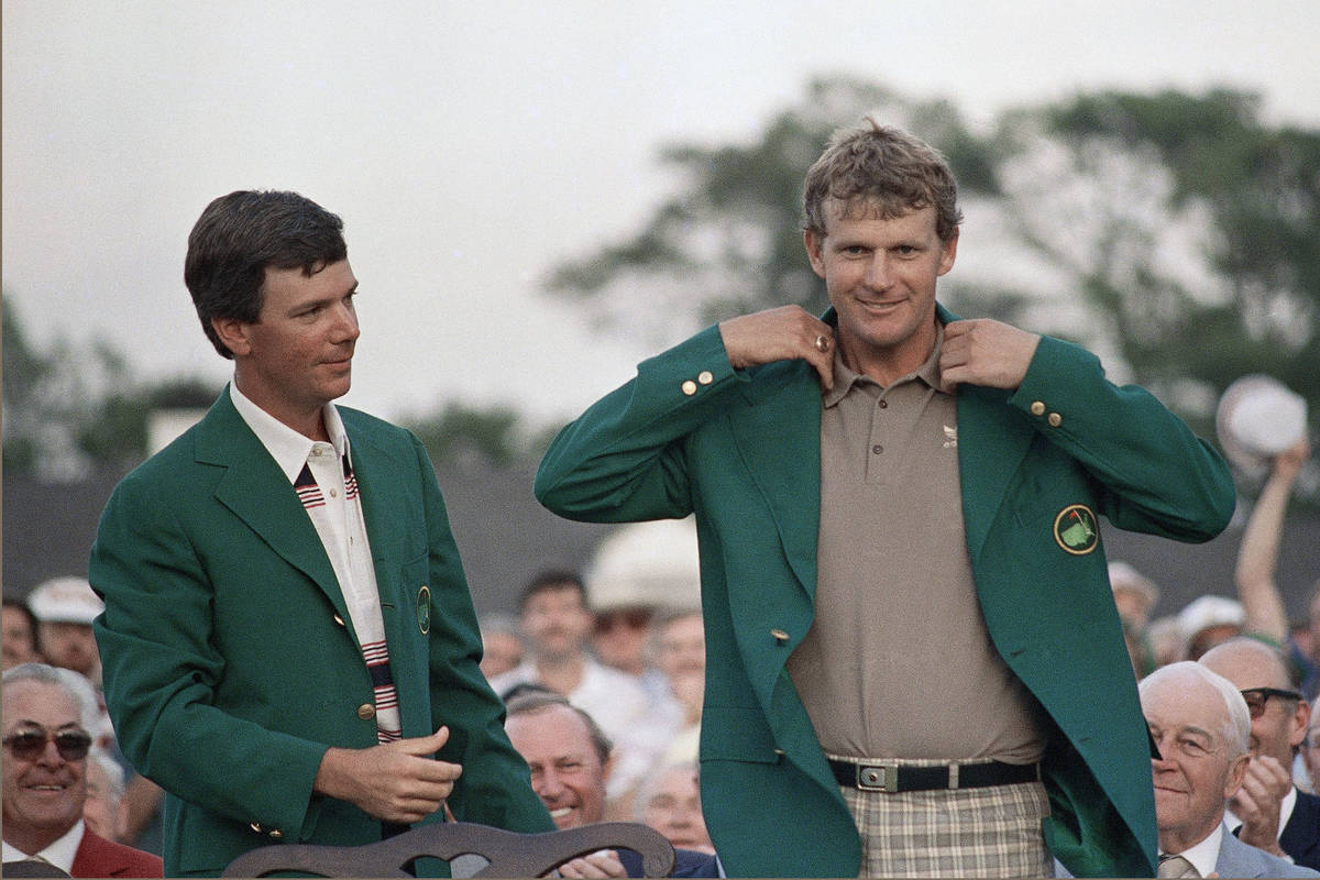 A smiling Sandy Lyle, right, is presented the Green Jacket of the Augusta National Golf Club af ...