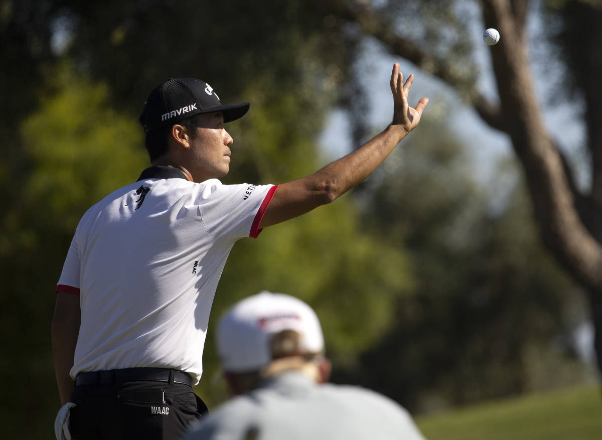 Kevin Na catches a ball from his caddy before putting the twelfth hole during the final round o ...