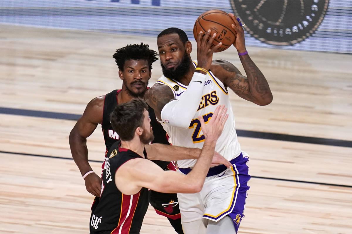 Los Angeles Lakers' LeBron James (23) drives against Miami Heat's Goran Dragic (7) and Jimmy Bu ...