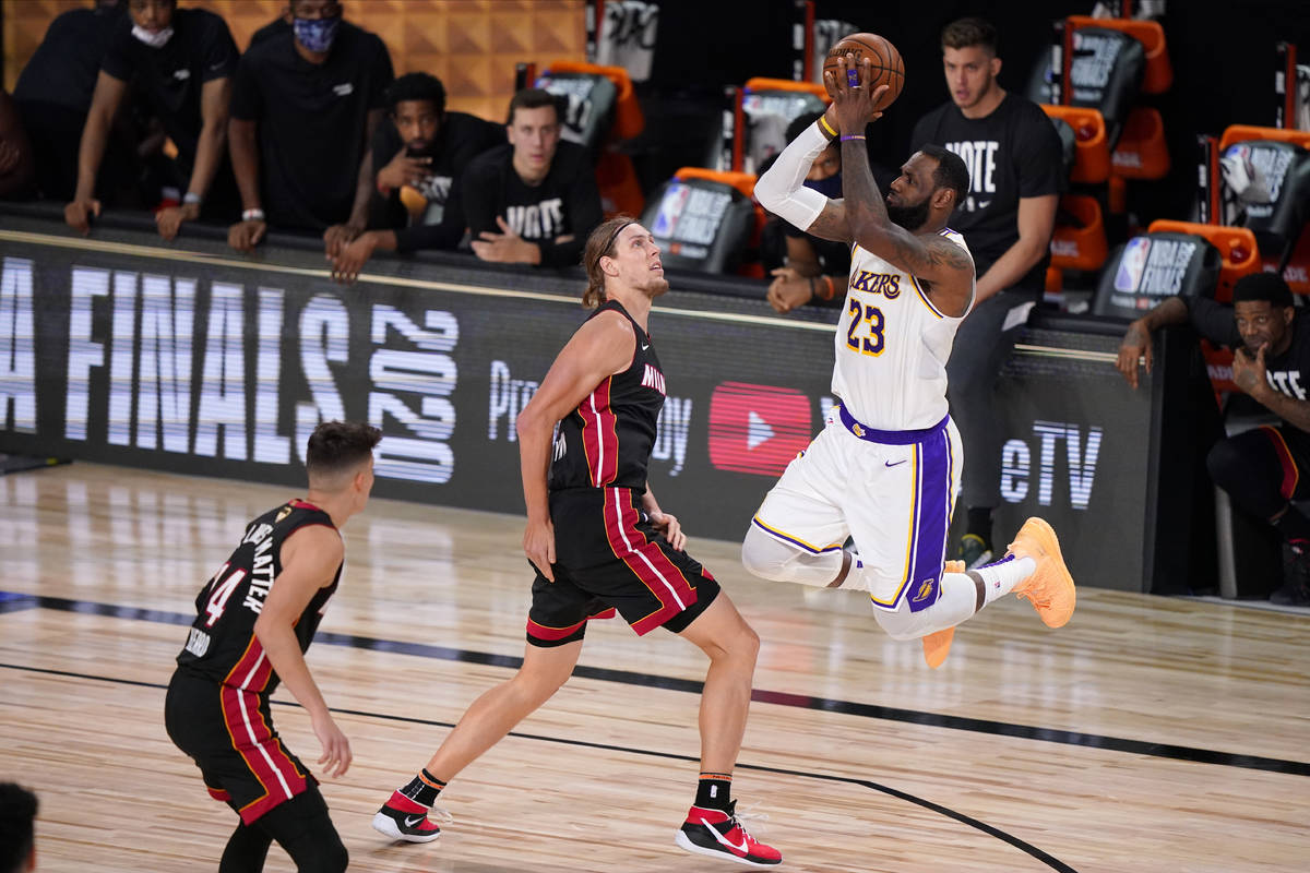 Los Angeles Lakers' LeBron James (23) takes a shot over Miami Heat's Kelly Olynyk (9) during th ...