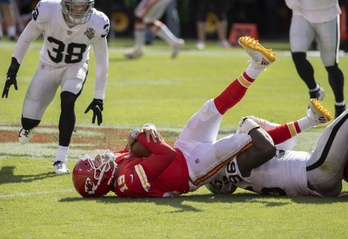 Kansas City Chiefs quarterback Patrick Mahomes (15) is tackled by Las Vegas Raiders defensive e ...