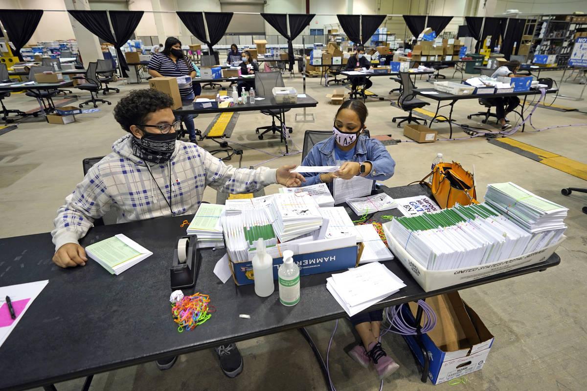 Harris County election workers Jose Vasquez, left, and Romanique Tillman prepare mail-in ballot ...