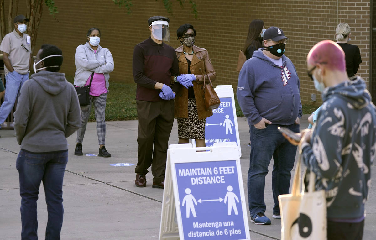 Signs remind voters to social distance as they line up outside Richardson City Hall for early v ...