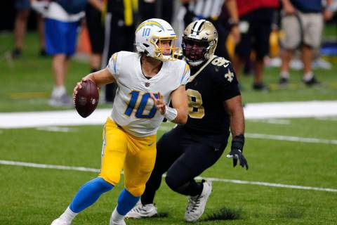 Los Angeles Chargers quarterback Justin Herbert (10) scrambles under pressure fromNew Orleans S ...