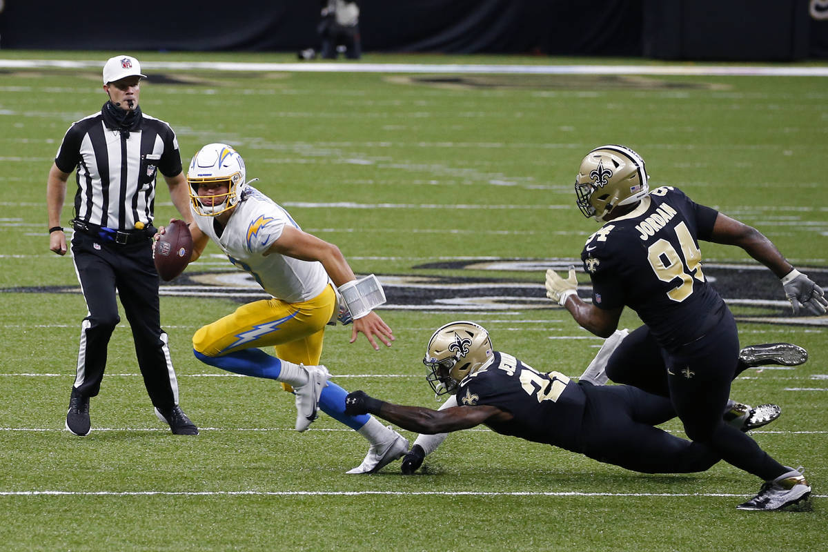 Los Angeles Chargers quarterback Justin Herbert scrambles under pressure from Los Angeles Charg ...