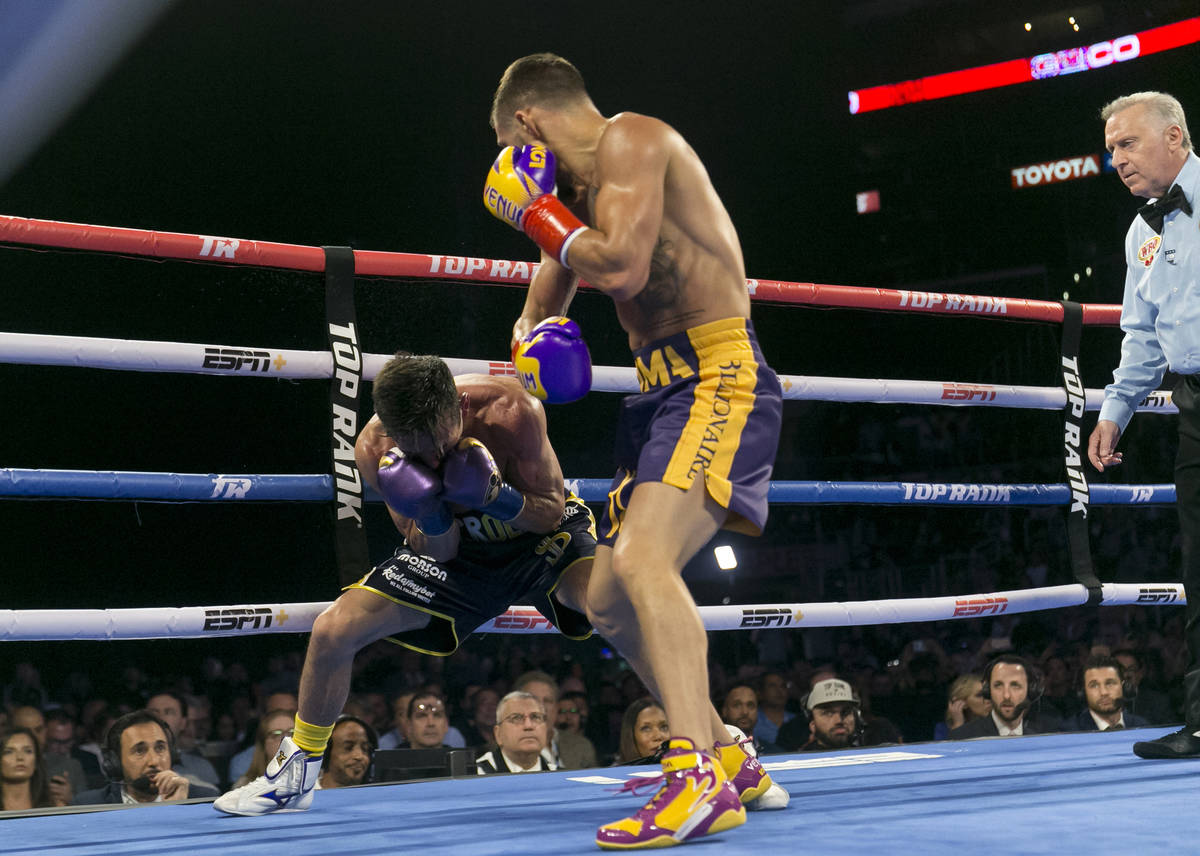 Vasiliy Lomachenko, right, from Ukraine, knocks down Anthony Crolla, from Britain, in the fourt ...