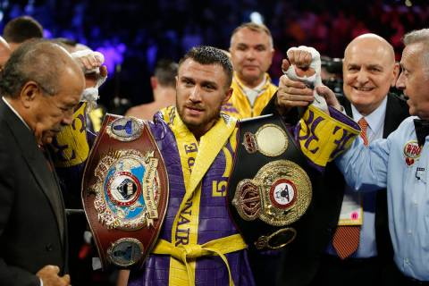 Vasiliy Lomachenko celebrates after defending his WBA/WBO lightweight titles after knocking out ...