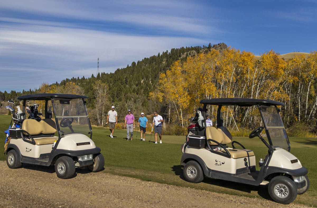 Players finish their round at the 18th hole of Rock Creek Cattle Company golf course on Friday, ...