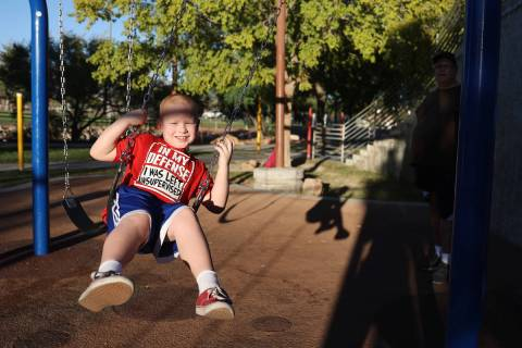 Joshua Farren, 7, with his father Anthony watching, swings at the Centennial Hills Park playgro ...