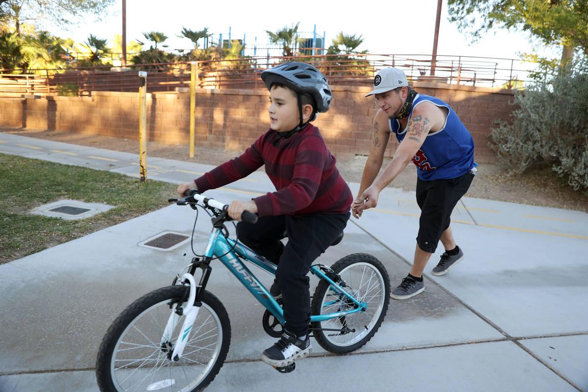 Corey Behm helps his son Jason, 8, ride his bike around the Centennial Hills Park playground in ...