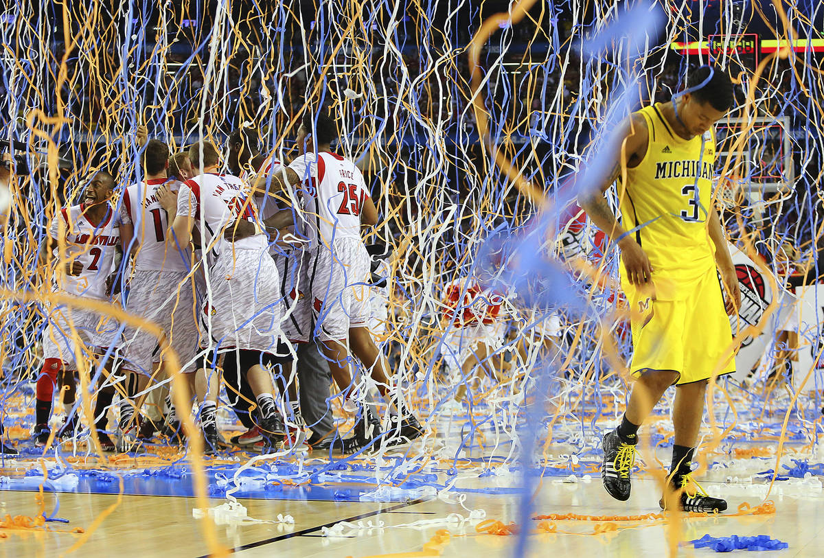 FILE - In this April 8, 2013, file photo, Michigan guard Trey Burke (3) walks off the court as ...