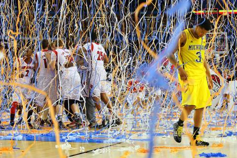 In this April 8, 2013, file photo, Michigan guard Trey Burke (3) walks off the court as confett ...