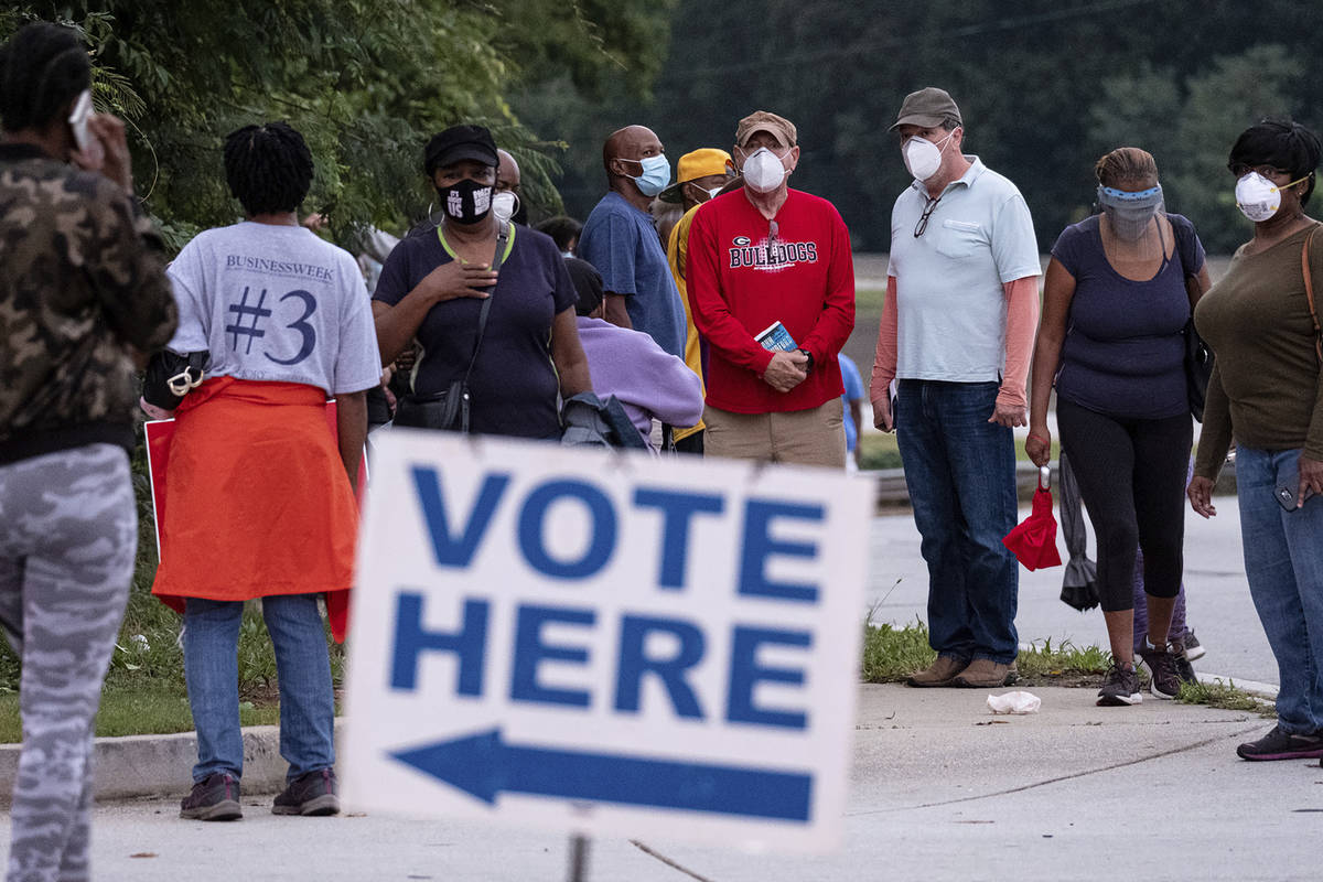 People wait in line to vote in Decatur, Ga., Monday, Oct. 12, 2020. (Ben Gray/Atlanta Journal-C ...