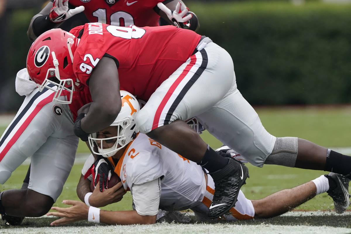 Tennessee quarterback Jarrett Guarantano (2) is brought down by Georgia defensive lineman Julia ...