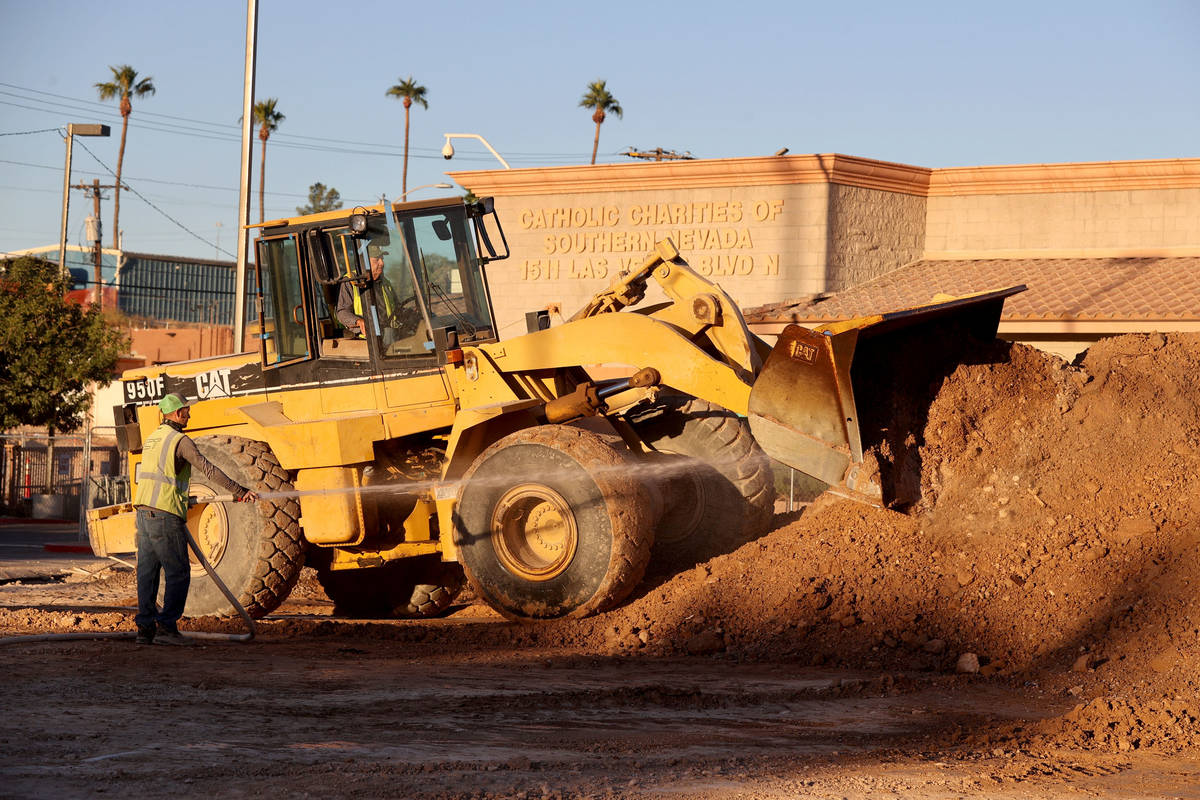Workers remove dirt from a former landscaped area at Catholic Charities of Southern Nevada Frid ...