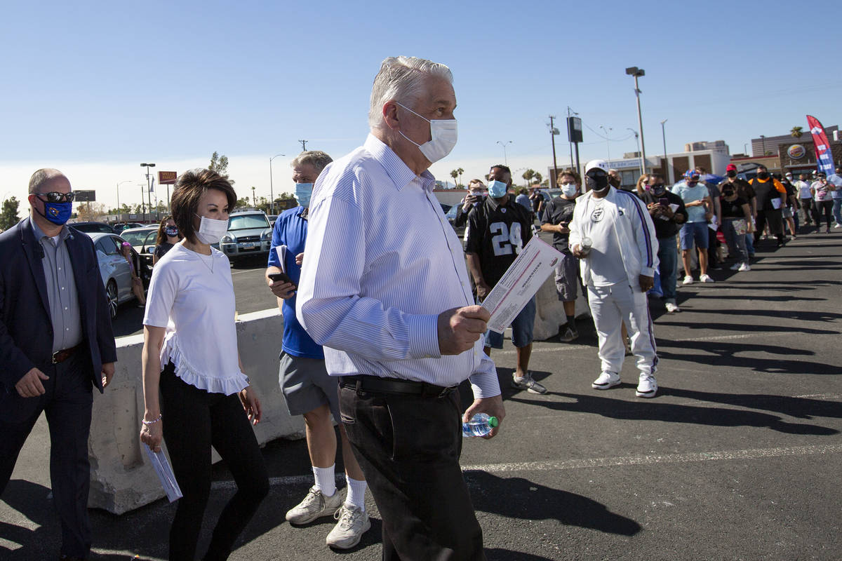Gov. Steve Sisolak and his family walk into the Boulevard Mall early voting location to drop of ...