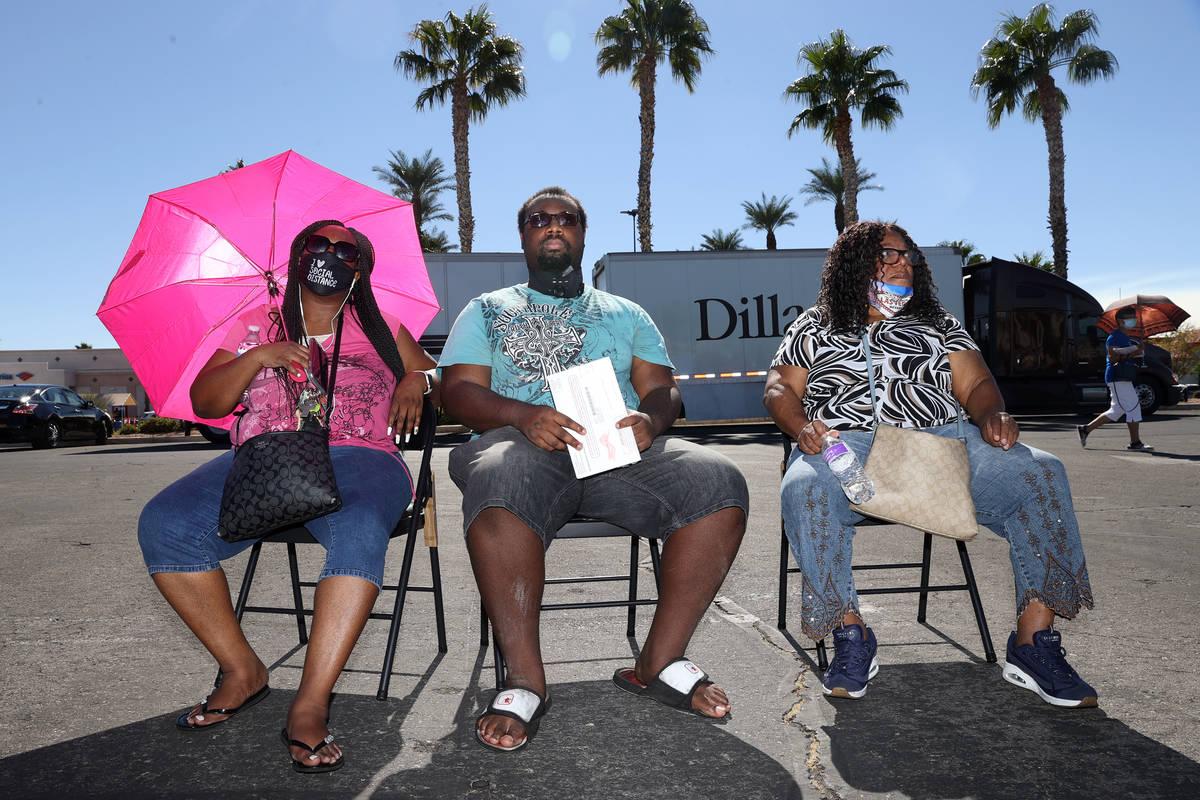 Jamailla Parks-El, from left, her son Daquan Smith and her mother Deborah Elaster, wait in line ...