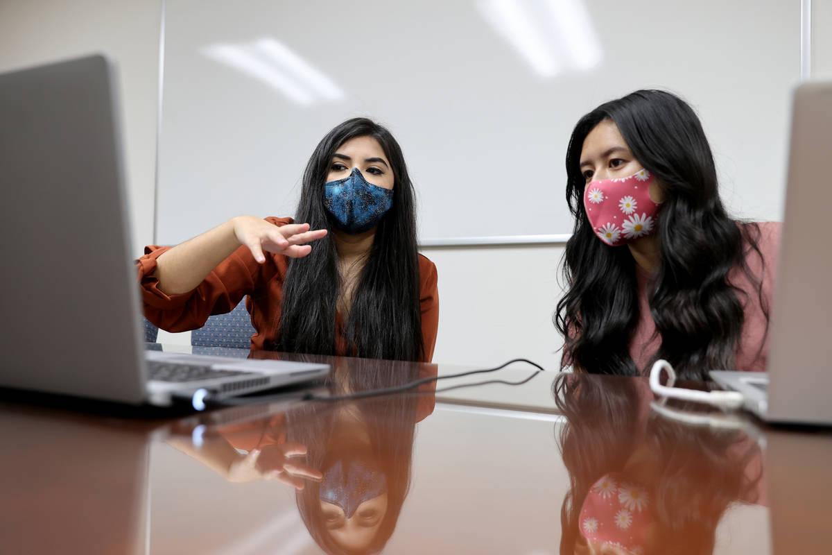 Karen Gutierrez, left, trains fellow UNLV student Leanne Villanueva on the school's COVID-19 co ...