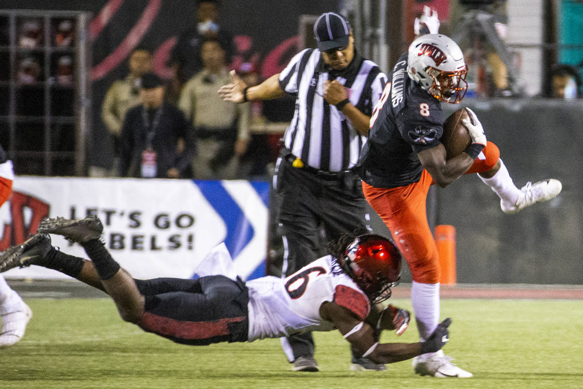 UNLV Rebels running back Charles Williams (8, right) attempts to escape a tackle attempt by San ...
