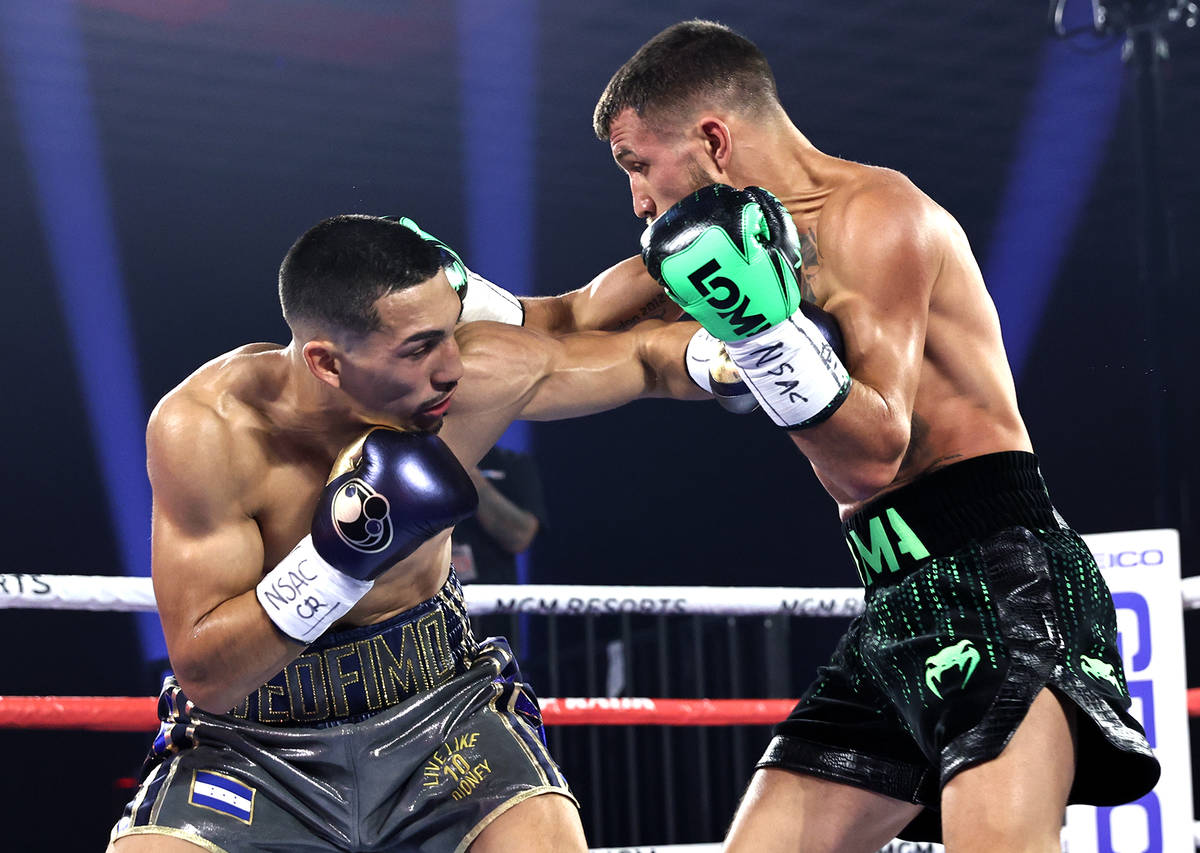 Teofimo Lopez, left, and Vasiliy Lomachenko trade punches during their lightweight title fight ...