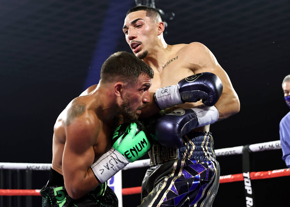 Vasiliy Lomachenko, left, lands a punch against Teofimo Lopez during their lightweight title fi ...