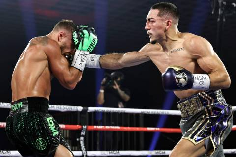 Teofimo Lopez, right, lands a punch against Vasiliy Lomachenko during their lightweight title f ...