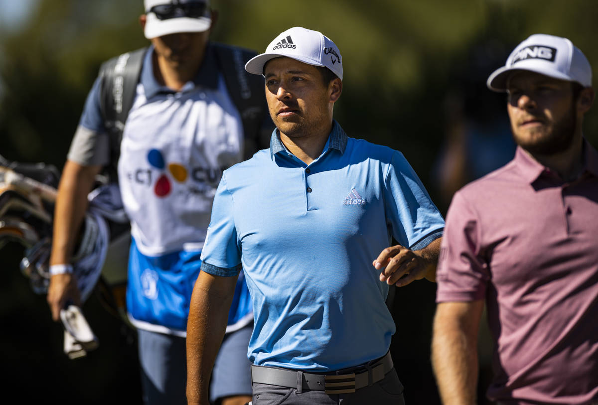 Xander Schauffele walks to the fifth green alonside Tyrrell Hatton, right, during the third rou ...