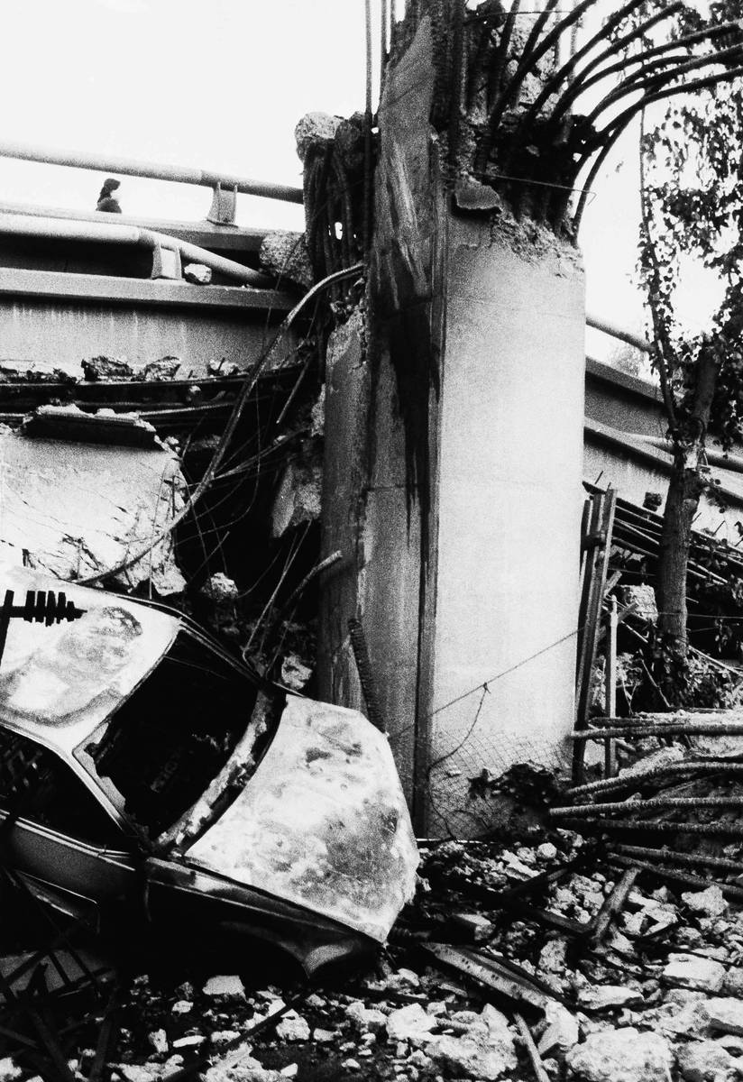 A burned out vehicle lies at the base of a broken column that once supported two decks of the C ...