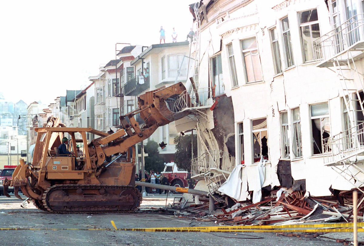 A bulldozer brings down a damaged apartment complex in the Marina district of San Francisco, Ca ...