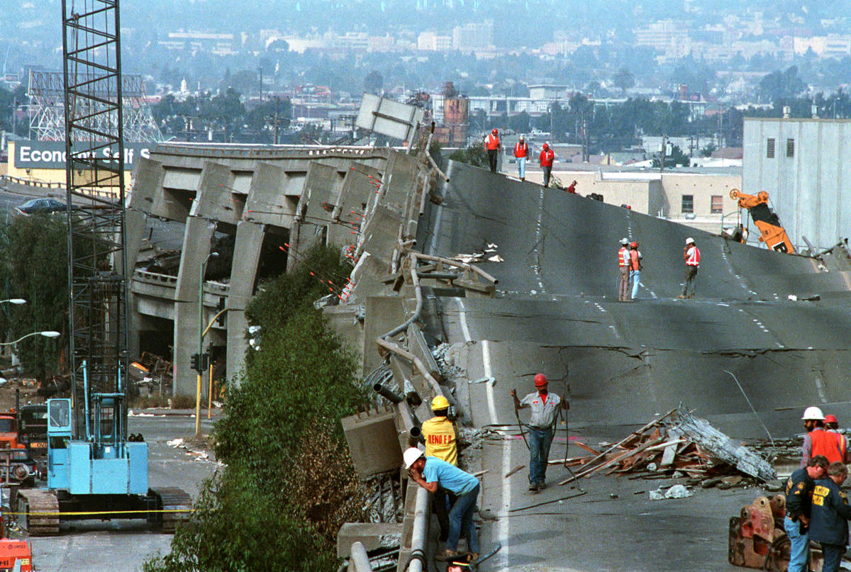 Workers check the damage to Interstate 880 in Oakland, Ca. on Thursday, Oct. 19, 1989. The fre ...