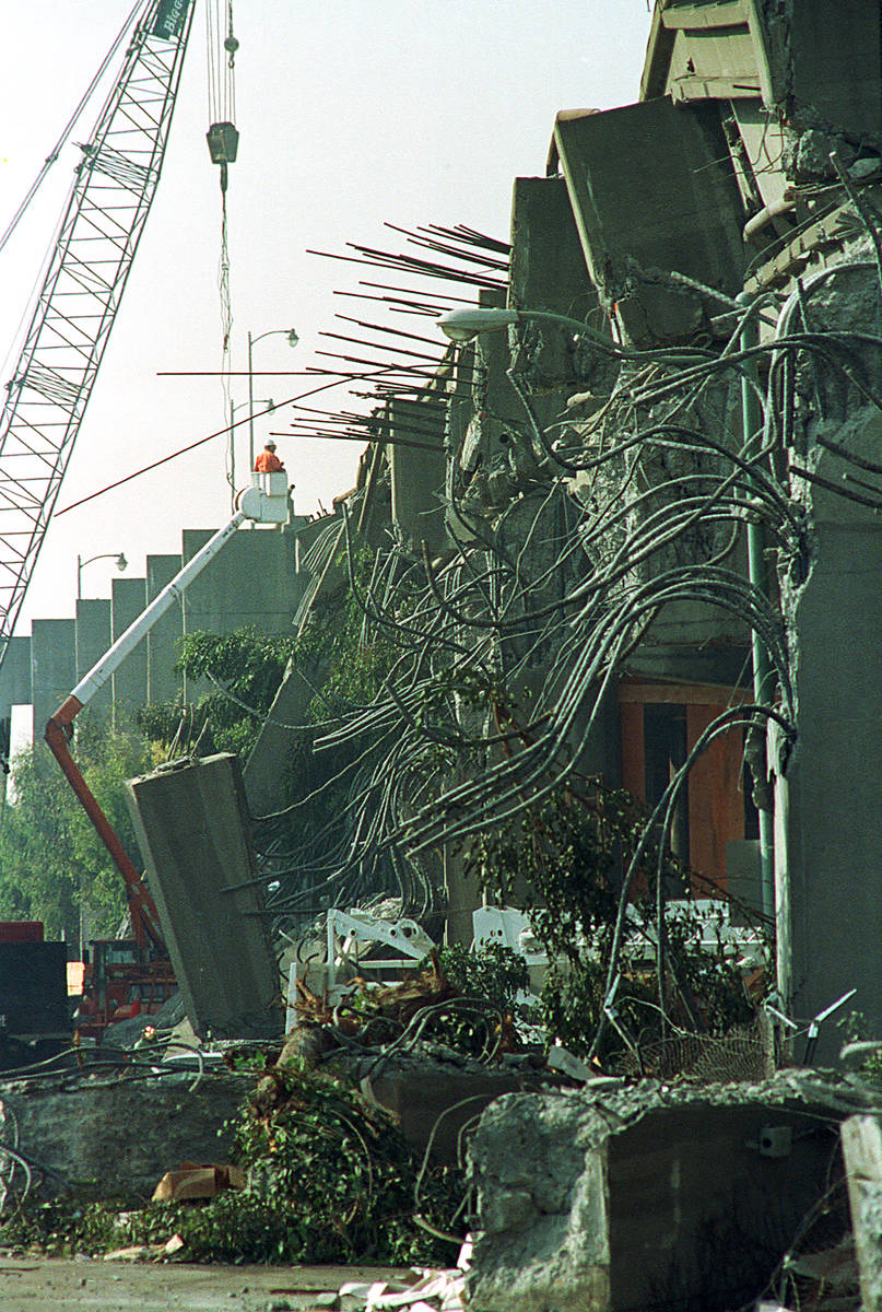 A crane lifts a worker as crews continue to clean up and search through twisted wreckage of the ...