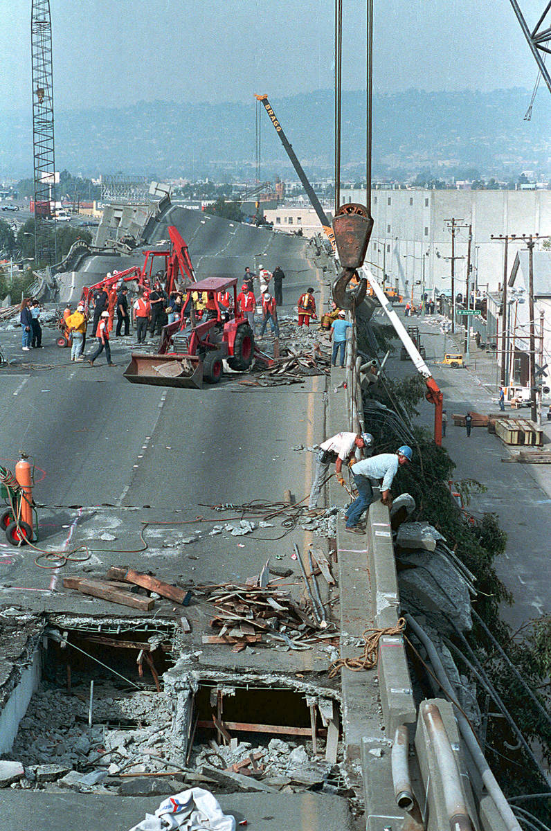Heavy equipment cranes and backhoes probe and lift debris from the crushed Interstate 880 freew ...