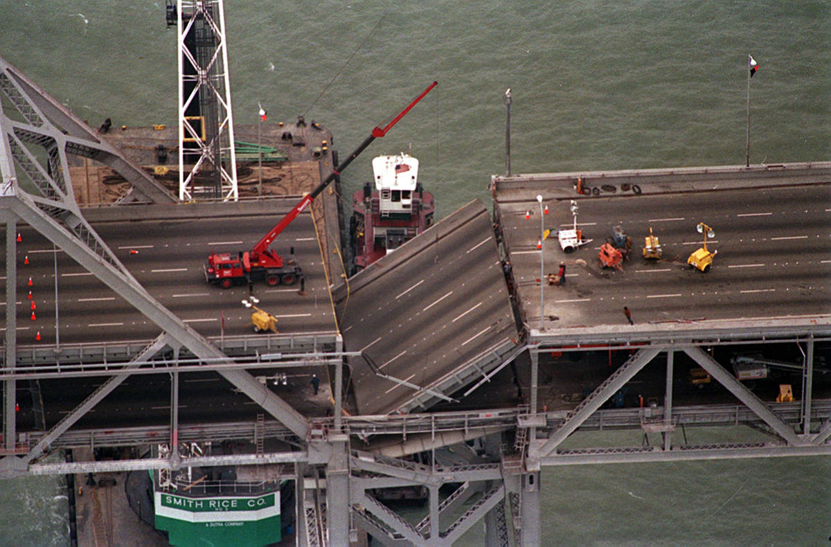 A crane mounted on a barge, left, has been towed into position, ready to lift a section of the ...
