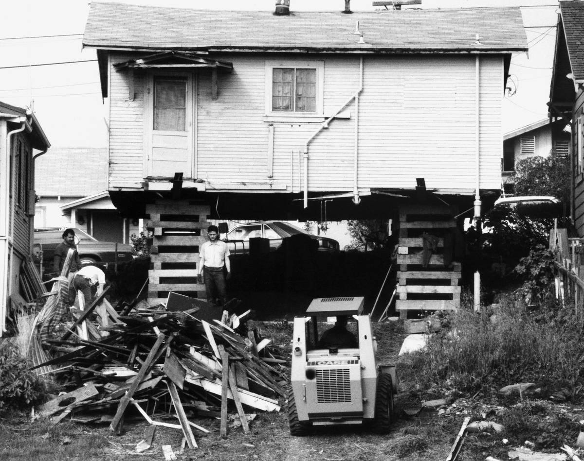 A construction crew works at marking repairs to an elevated and exposed house on a hill, Tuesda ...