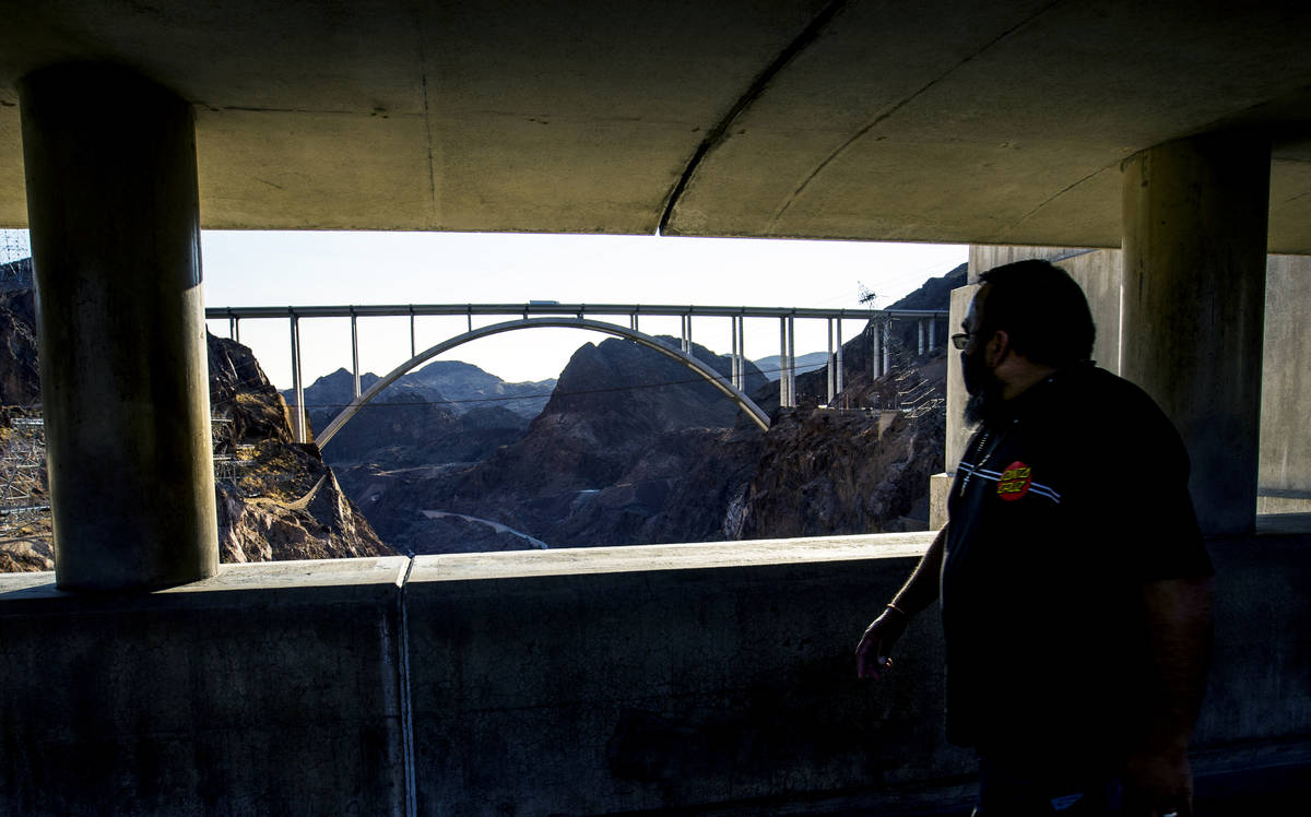 A visitor walks along the top of the Hoover Dam, which opened to the public after being closed ...