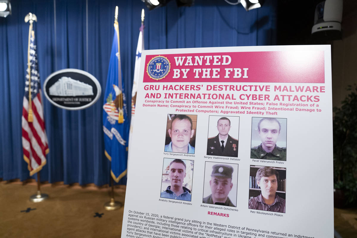 A poster showing six wanted Russian military intelligence officers is displayed before a news c ...