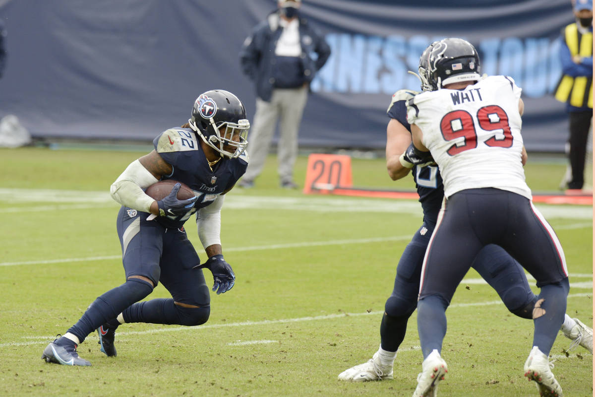 Tennessee Titans running back Derrick Henry (22) tries to get past Houston Texans defensive end ...