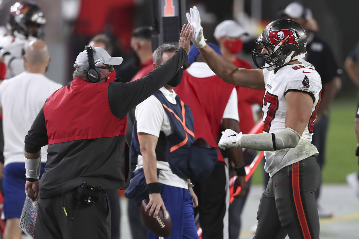 Tampa Bay Buccaneers head coach Bruce Arians high fives tight end Rob Gronkowski (87) as he lea ...