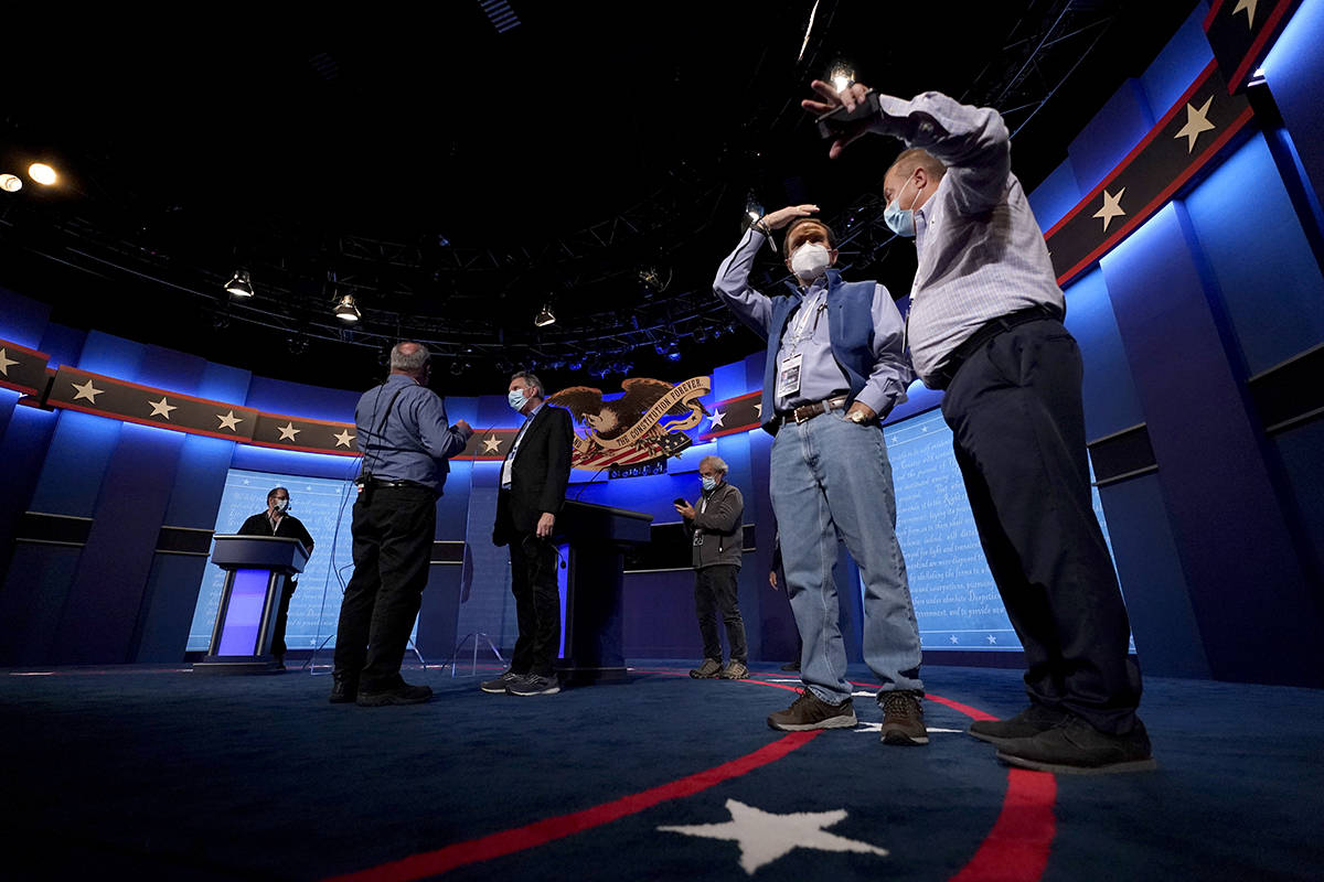 Production crew member stand on stage ahead of the final presidential debate between Republican ...