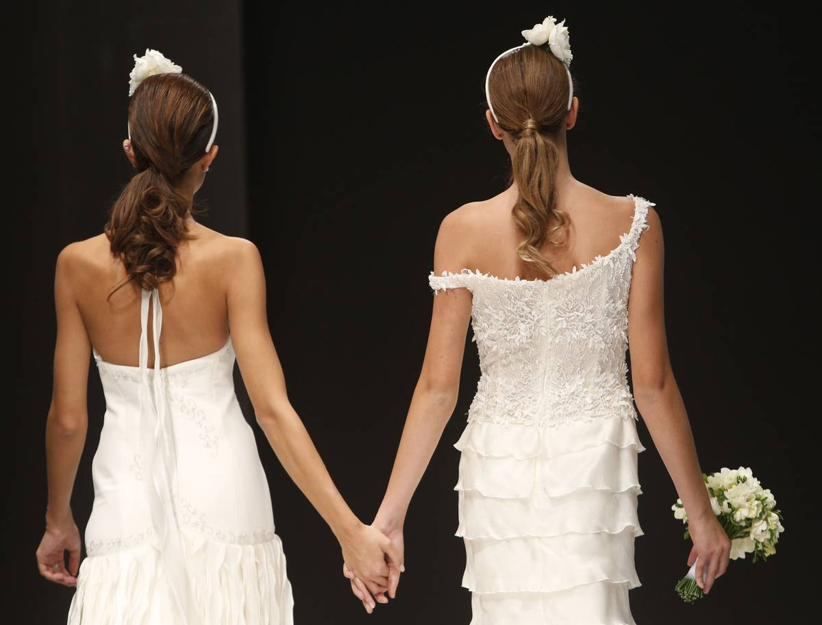 FILE -- In this Thursday, Oct. 23, 2014 file photo, models hold hands on the catwalk during a w ...