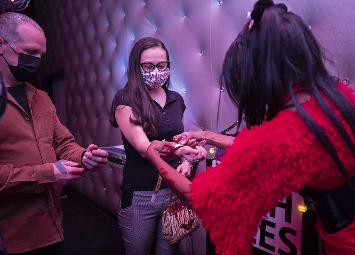 Eric Rypka, of Las Vegas, left, and Yocelin Lizarraga, of Las Vegas, center, receive wrist band ...