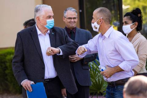 Gov. Steve Sisolak, left, elbow bumps Hans Hippert, owner of Jojo's Jerky, after a press confer ...